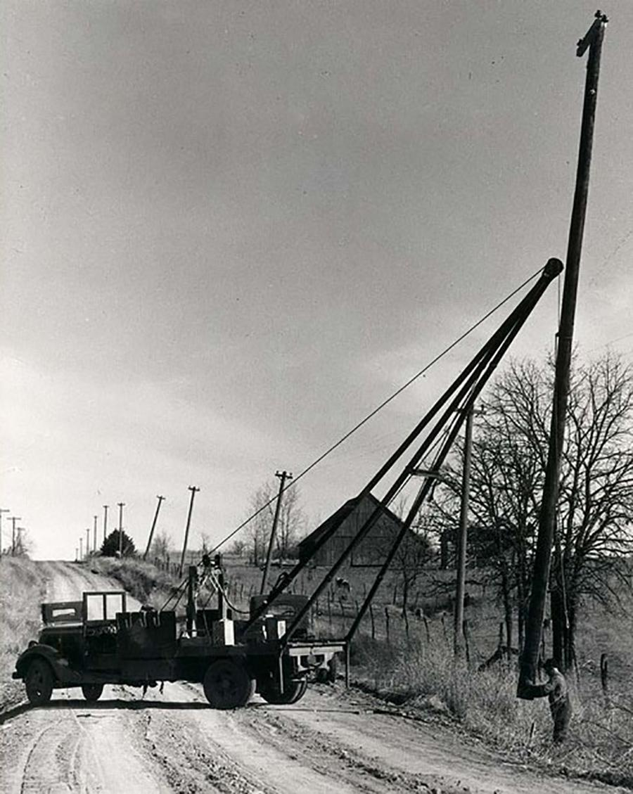 black and white photo of a truck setting an electric pole