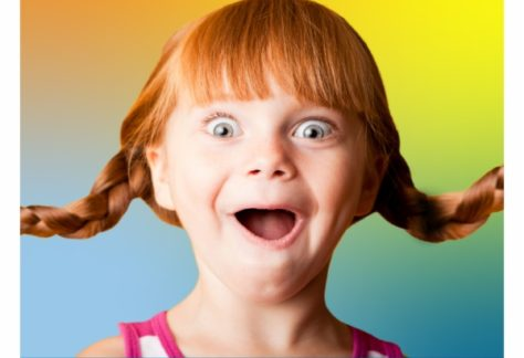 little girl looking excited on a rainbow back drop